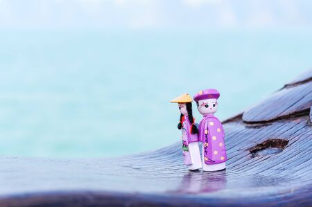Handicraft Vietnamese magnetic wooden puppets in traditional costumes with natural ocean background. Famous Vietnamese dolls souvenirs. Selective focus on the face of the puppets