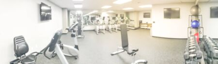 Panorama abstract blurred empty fitness center at modern hotel in Seattle, Washington, US. Row of treadmill, elliptical, strider, dumbbell stand and workout equipment. Large wall mount mirror, TVs Stock Photo