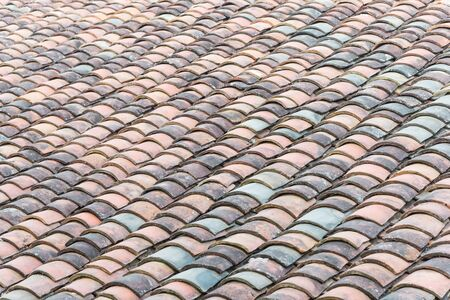 Close-up view curved clay tiled roof in various colors from an old house in North Vietnam, late afternoon light. Ancient, weathered roof tile surface, moss texture. Natural seamless pattern background