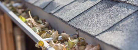 Vue panoramique sur la gouttière obstruée près des bardeaux du toit d'une maison d'habitation pleine de feuilles séchées et d'un besoin sale de nettoyage. Tuyau de vidange bloqué sur le toit. Nettoyage de gouttière, concept d'entretien à domicile