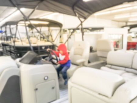 Abstract blurred Asian toddler boy in warm clothes try test driving at large dealer selling variety of new and used boats near Dallas, Texas, USA. Recreational boat buying and servicing concept Stock fotó