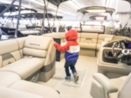 Abstract blurred Asian toddler boy in warm clothes try test driving at large dealer selling variety of new and used boats near Dallas, Texas, USA. Recreational boat buying and servicing concept Imagens - 134209515