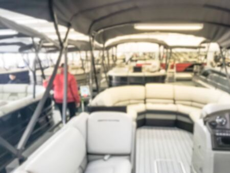 Blurred motion Asian customers in warm clothes try test driving at large dealer selling variety of new and used boats near Dallas, Texas, USA. Recreational boat buying and servicing concept Imagens - 134209520