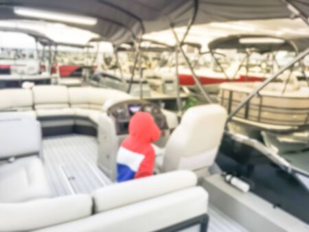 Abstract blurred Asian toddler boy in warm clothes at large dealer selling variety of new and used boats near Dallas, Texas, USA. Recreational boat buying and servicing concept