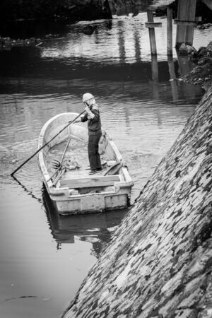 Toned image female worker cleaning a polluted canal full of dark water and variety of wastes in Hanoi. Pollution is one of the most serious problems of Vietnam. Crew in face mask and helmet