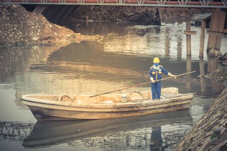 Cleaning a polluted canal full of dark water and variety of wastes near bridge in Hanoi. Pollution is one of the most serious problems of Vietnam. Female crew in face mask and helmet Imagens - 134657163