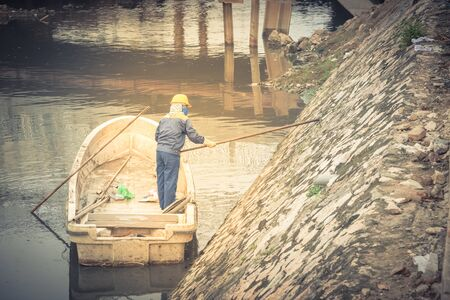 Polluted river in Hanoi with high embankment, retaining wall and a female worker is cleaning variety of wastes on the canal. Pollution is one of the most serious problems of Vietnam Stock fotó