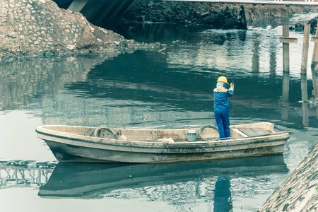 Rear view female worker cleaning a polluted canal full of dark water and variety of wastes in Hanoi. Pollution is one of the most serious problems of Vietnam. Crew in face mask and helmet Imagens - 134657175