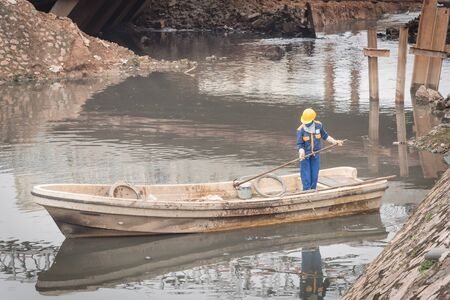 Polluted river in Hanoi with high embankment, retaining wall and a female worker is cleaning variety of wastes on the canal. Pollution is one of the most serious problems of Vietnam Imagens - 134657321