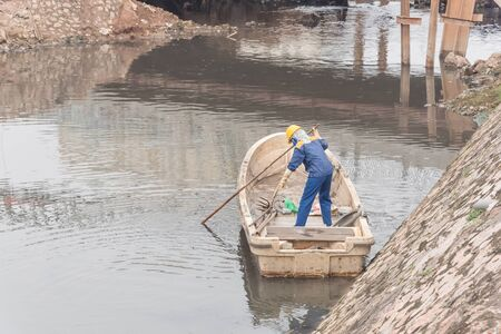 Polluted river in Hanoi with high embankment, retaining wall and a female worker is cleaning variety of wastes on the canal. Pollution is one of the most serious problems of Vietnam Imagens - 134657357