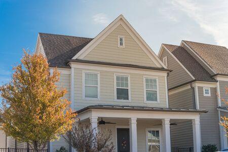 Case di lusso in stile cottage nella periferia di Dallas, in Texas, con rivestimenti in legno, veranda coperta con ventilatori a soffitto. Foglie autunnali colorate e isolamento termico dello strato di rivestimento bianco, resistenza agli agenti atmosferici