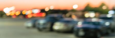 Panorama view abstract blurred parking lot of modern shopping center in Houston, Texas, USA. Exterior mall complex with row of cars in outdoor uncovered parking, bokeh light poles in background