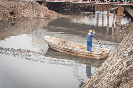 Cleaning a polluted canal full of dark water and variety of wastes near bridge in Hanoi. Pollution is one of the most serious problems of Vietnam. Female crew in face mask and helmet Stock fotó