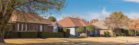 Panorama view typical bungalow style house in Dallas, Texas suburbs during fall season with colorful autumn leaves. Middle class neighborhood single story residential home with mature tree