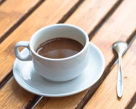 Popular Vietnamese milk coffee in ceramic cup and saucer with stainless spoon on outdoor wooden table. Top view a morning Vietnamese gourmet drink. Food concept. Imagens - 134657133