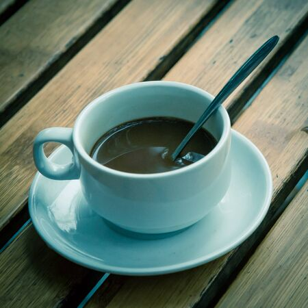 Toned photo of Popular Vietnamese milk coffee in ceramic cup and saucer with stainless spoon on outdoor wooden table. Top view a morning Vietnamese gourmet drink. Food concept.