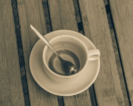 Empty cup of traditional Vietnamese milk coffee on outdoor wooden table. Popular white ceramic cup and saucer. Imagens - 134657140