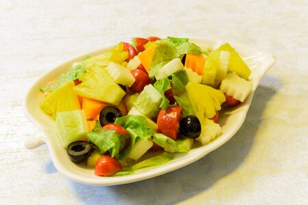 Fresh dish of mixed organic fruits salad with pineapple, cucumber, apple, cherries tomatoes, lettuce, carrot, olive. Colorful and healthy fiber in white leaf shape plate.