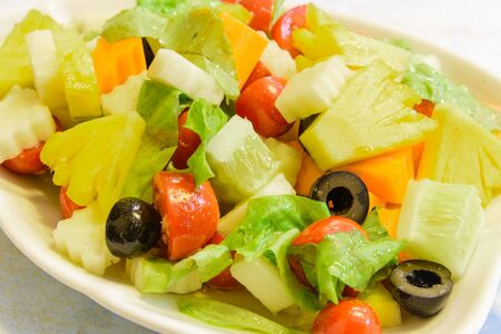 Close-up fresh dish of mixed organic fruits salad with pineapple, cucumber, apple, cherries tomatoes, lettuce, carrot, olive. Colorful and healthy fiber in white leaf shape plate. Imagens - 134657145