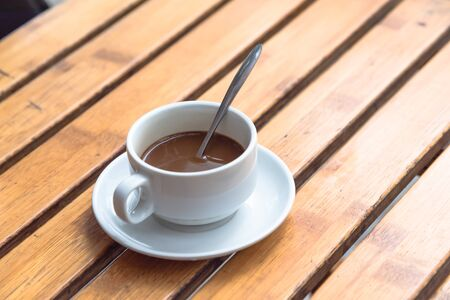 Popular Vietnamese milk coffee in ceramic cup and saucer with stainless spoon on outdoor wooden table. Top view a morning Vietnamese gourmet drink. Food concept.