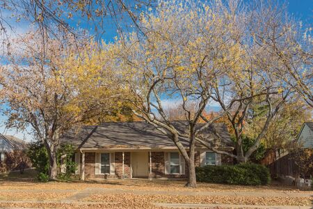 Typical bungalow style house in Dallas, Texas suburbs during fall season with colorful autumn leaves. Middle class neighborhood with single story residential home with mature tree, cloud blue sky Stock fotó