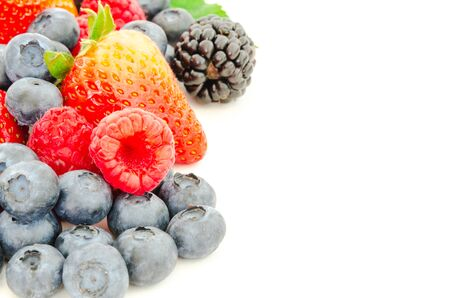 Assortment of blackberries, strawberries, blueberries and raspberries isolated on white background. Pile of variety organic and fresh pick berries with clipping path and copy space. Stock fotó