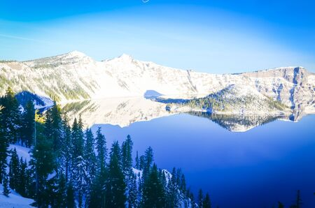 Snow cliff and pine trees lush above Crater Lake with snowcap mountain reflection. During cold snaps fingers of ice probe from the shore out over the abyss. Winter scene at National Park, Oregon Zdjęcie Seryjne