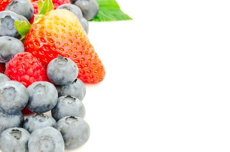 Green leaves and arrangement of strawberries, blueberries and raspberries isolated on white background. Pile of variety organic and fresh pick berries with clipping path and copy space.
