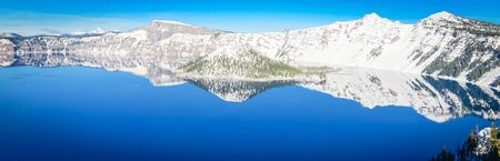 Panorama view mirror reflection of snowcap mountain and Wizard Island on Crater Lake, Oregon, USA. Crystal clear blue water and Northwest sky. Winter scene at Crater Lake National Park volcano