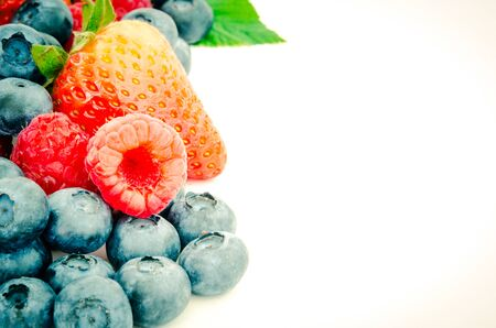 Toned photo arrangement of strawberries, blueberries and raspberries isolated on white background. Pile of variety organic and fresh pick berries with clipping path and copy space. Imagens - 134658766
