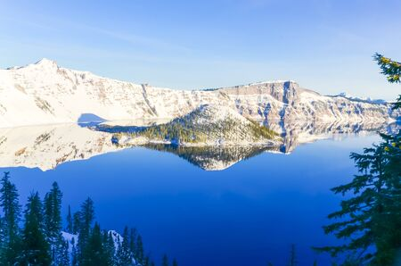 Snow cliff and pine trees lush above Crater Lake with snowcap mountain reflection. During cold snaps fingers of ice probe from the shore out over the abyss. Winter scene at National Park, Oregon Archivio Fotografico