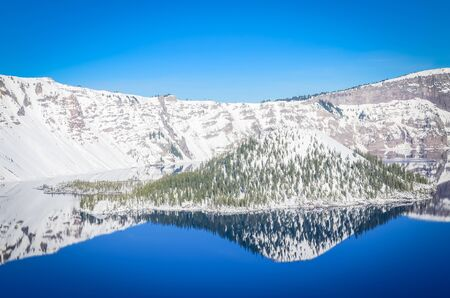 Mirror reflection of snowcap mountain and Wizard Island on Crater Lake, Oregon, USA. Crystal clear blue water and Northwest sky. Winter scene at Crater Lake National Park volcano Zdjęcie Seryjne