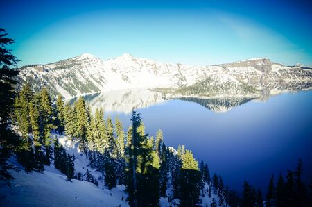 Pine trees lush cliff and mirror reflection of snowcap mountain and Wizard Island on Crater Lake, Oregon, USA. Winter scene at Crater Lake National Park volcano