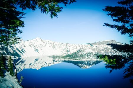 Beautiful winter scene from viewpoint cliff at Crater Lake with pine tree lush and reflection of snowcap mountain and Wizard Island. National Park in Oregon, USA.