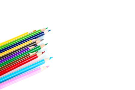 Side view pile of colored pencils isolated on white background. Bunch of assorted school supplies in rainbow arrangement. Back to school and creativity concept, clipping path and copy space