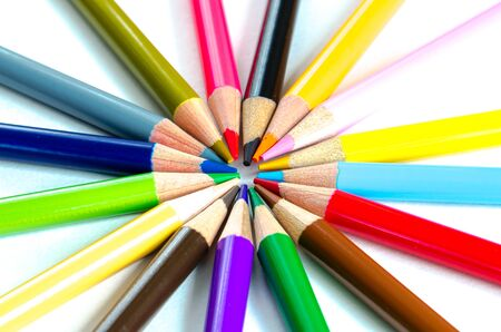 Circle pattern of colored pencils isolated on white background. Bunch of assorted school supplies in rainbow arrangement. Back to school and creativity concept, education background Imagens - 134658927