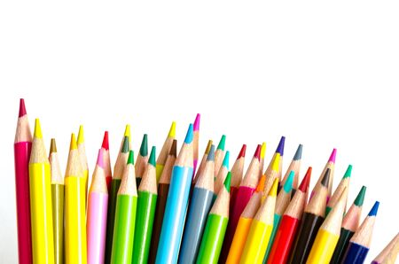 Top view pile of colored pencils isolated on white background. Bunch of assorted school supplies in rainbow arrangement. Back to school and creativity concept, clipping path and copy space