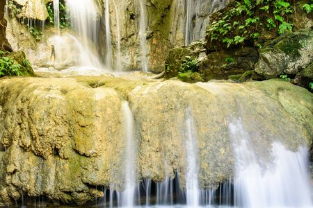 Large round limestone rock with soft silk stream gushing through at Thac Voi waterfall of tropical rainforest in Thanh Hoa province, Vietnam 写真素材