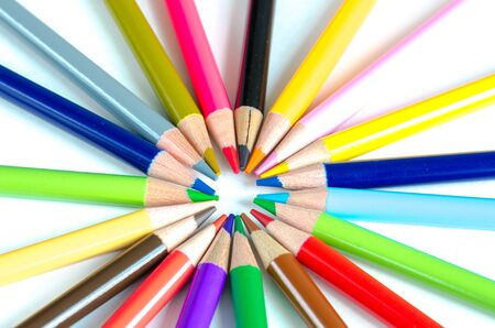Circle pattern of colored pencils isolated on white background. Bunch of assorted school supplies in rainbow arrangement. Back to school and creativity concept, education background