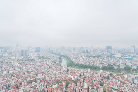 Aerial high-density housing surrounding To Lich river in Cau Giay District, Hanoi, Vietnam. Hanoi has thousands of high-rise buildings in urban sprawling as rising demand. Foggy or polluted air 写真素材