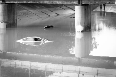 Top view swamped car under a tollway bridge near downtown Houston, Texas. Two sedan flooded under elevated highway road by heavy rain hurricane. Banco de Imagens