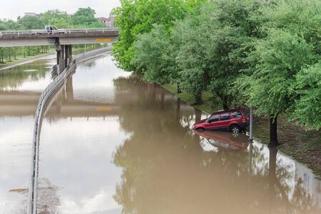 Swamped car by flood water near downtown Houston, Texas, USA. Flooded car under deep water on a heavy high water road. Disaster Motor Vehicle Insurance Claim Themed. Severe weather concept