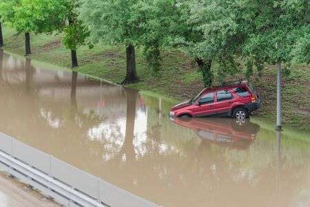 Close-up swamped car by flood water near downtown Houston, Texas, USA. Flooded car under deep water on a heavy high water road. Disaster Motor Vehicle Insurance Claim Themed. Severe weather concept