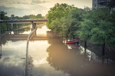 Überschwemmtes Auto durch Hochwasser in der Nähe der Innenstadt von Houston, Texas, USA. Überschwemmtes Auto unter tiefem Wasser auf einer schweren Hochwasserstraße. Schaden-Kfz-Versicherungsanspruch unter dem Motto. Unwetterkonzept