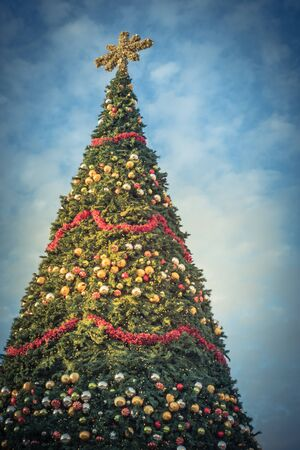 Toned photo of 60 foot Christmas tree with snowflake top, ornament balls and efficient LED lights display at sunset. Typical Xmas decoration at upscale shopping center in Texas, America Фото со стока