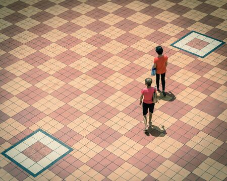 Directly above view two Asian ladies walking on patio tiles outdoor in Singapore