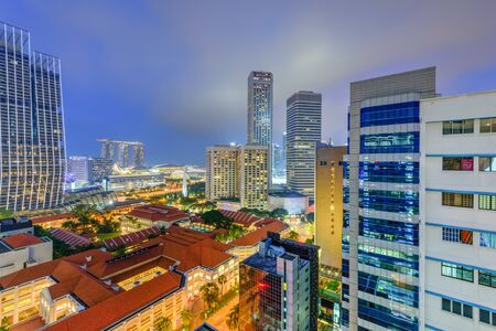 Aerial view public residential condominium building complex and downtown skylines at Bugis neighborhood in Singapore at blue hour.