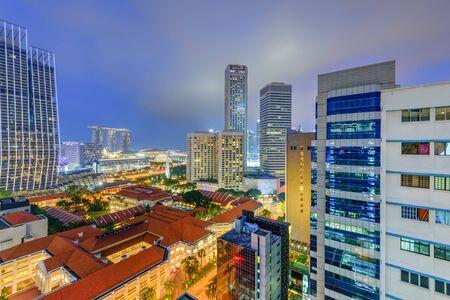 Luftbild öffentliche Wohnanlage Gebäudekomplex und Skylines der Innenstadt im Stadtteil Bugis in Singapur zur blauen Stunde.