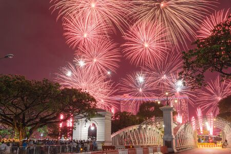 Beautiful firework display with silhouette of crowded people watching in New Year Eve celebration in Singapore. Colorful festive background. Stock Photo