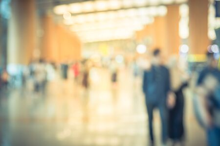 Abstract blurred passengers in an Asian airport background. Motion blur crowed of people walking along the hallway with natural light from skylight roof windows. Stock Photo